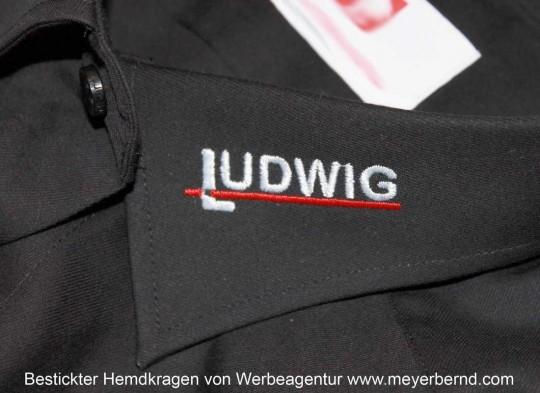 """Bestickter Hemdkragen eines schwarzen Hemdes mit Firmenlogo """"Ludwig"""" in Silber und Rot."""
