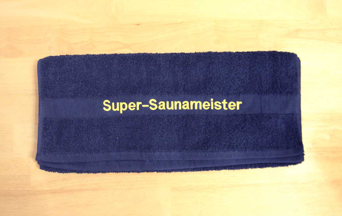 """Besticktes Handtuch aus dunkelblauem Frotteestoff mit einer gelben Bestickung """"Super-Saunameister"""" auf der Borte"""