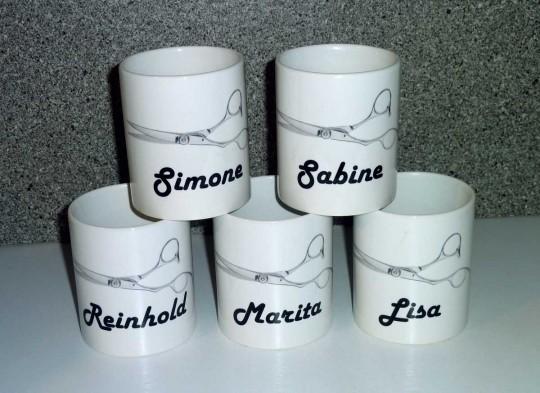 Fünf bedruckte Tassen mit Friseurschere und Namen der Mitarbeiter für einen Friseursalon