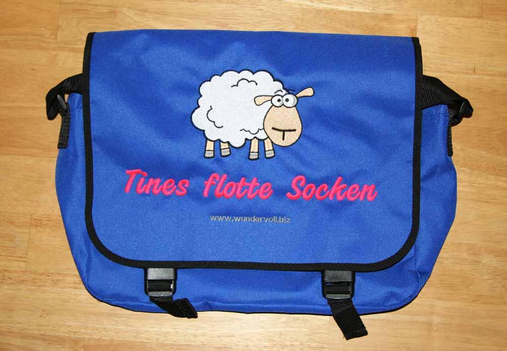 Wir bieten Stickereien auf Textilien an. Hier haben wir eine blaue Tasche mit einem Schaf bestickt