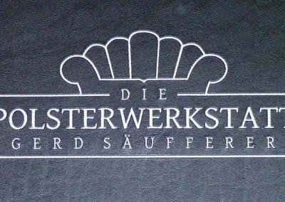 Logo der Polsterwerkstatt Gerd Säufferer in dezentem Silber auf schwarzem Kunstleder.