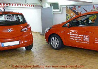 """Zwei von uns beschriftete Opel Corsa in rot mit weißer Folienbeschriftung """"Diakonie- und Sozialstation Schurwald"""" auf den Seiten und der Heckscheibe"""