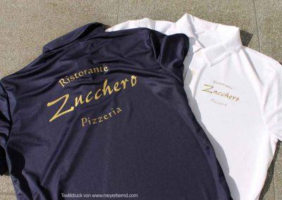 Mit Goldfolie bedruckte blaue und weiße Poloshirts. Bedruckt mit dem Logo: Ristorante Pizzeria Zucchero aus Lindorf
