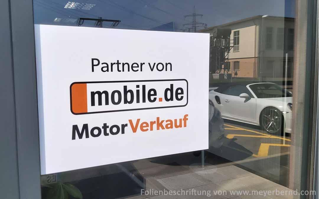 """Weiße, rechteckige Klebefolie auf dem Glasfenster eines Autohauses mit dem Text: """"Partner von mobile.de MotorVerkauf"""""""
