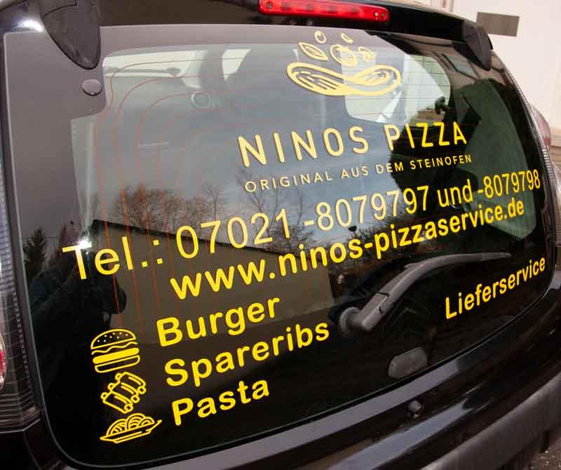 Heckscheibenbeschriftung Ninos Pizzaservice aus Kirchheim teck auf Glasscheibe mit Logo, Kontaktdaten und stilisierten Beispielen, wie Burger, Spareribs und Pasta